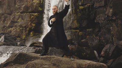Kung Fu Master Performing Martial Arts By Waterfall