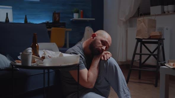 Homme déprimé assis sur le sol regardant la caméra avec expression désavouée