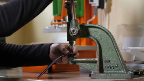 Hands of Craftsman Inserting Rivet Into Leather