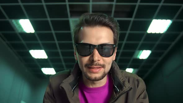 Man in Sunglasses Sits Down in Front of Camera Says Something
