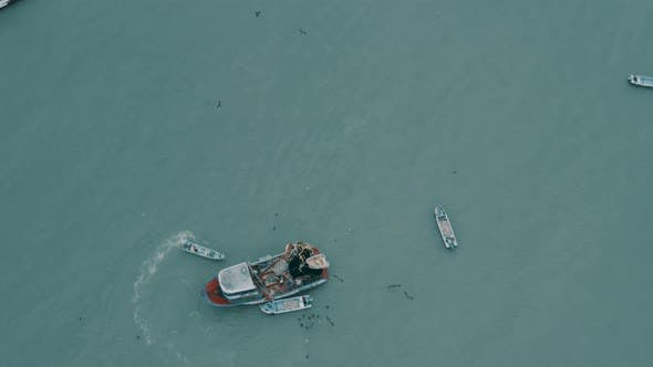 Aerial footage flying over a small fishing boat unloading its harvest