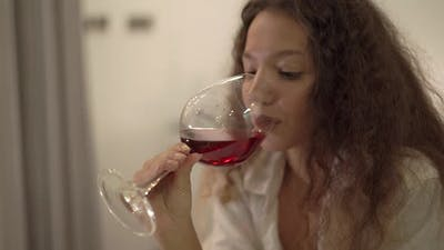 Young Woman Brunette in White Shirt Tastes Alcohol Beverage