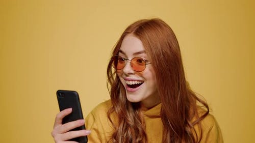 Surprised Girl Getting Good News on Mobile Phone