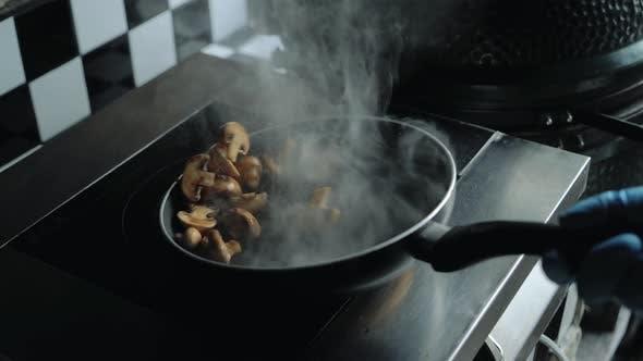 Chef kocht Pilze in einer Pfanne.