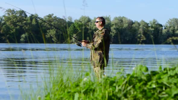 Fisherman Enjoys Outdoor Recreation, Fishing for Spinning and Enjoying His Catch