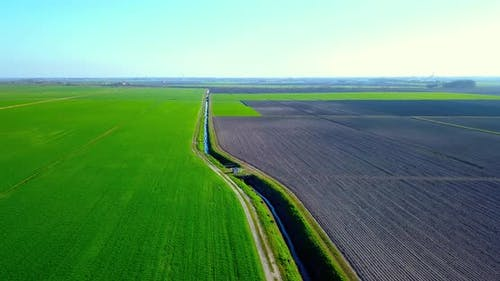 Irrigation Canal Divides Green Field and Plowed Terrain