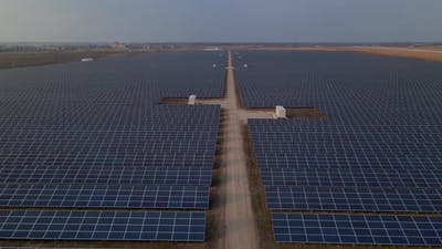 Aerial Drone View Into Large Solar Panels at a Solar Farm at Early Spring Sunset