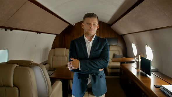Thumbnail for Confident Business Man with Crossed Arms Inside of Private Jet Seriously Looking at You