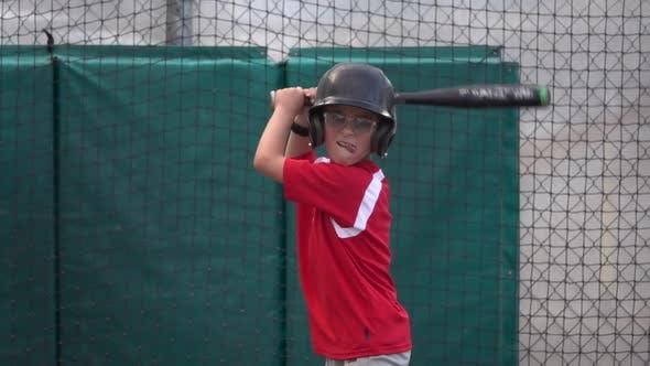 Thumbnail for Ein Junge praktiziert Baseball an einem Wimpfkäfig.