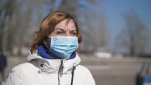 Thumbnail for Confident Blonde Woman in a Sanitary Mask Standing on Dnipro Quay in Spring