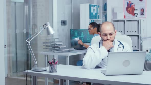 Thumbnail for Man Doctor Typing on Laptop in Modern Office