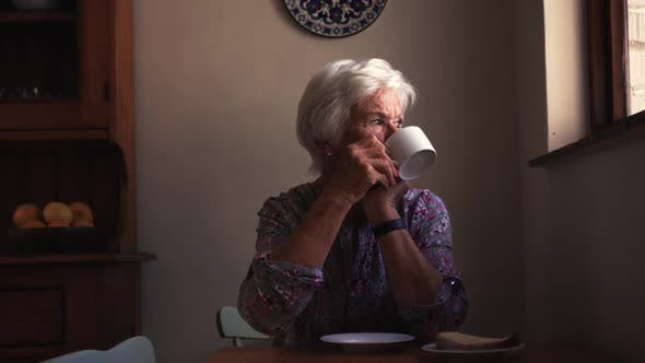 Thumbnail for Woman drinking coffee on dining table in kitchen at home 4k