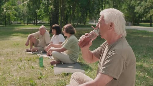 Senior Man Drinking Water during Outdoor Yoga Classes