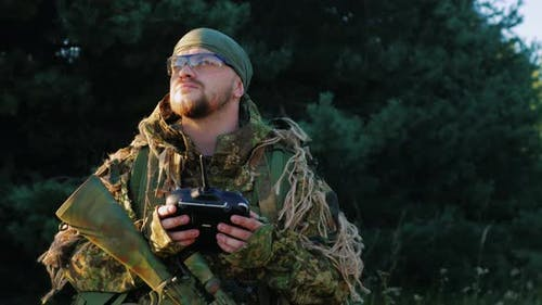 Armed Men in Camouflage Uses a Remote Control