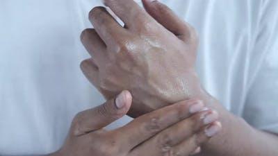 Man Hand Applying Petroleum Jelly on Skin
