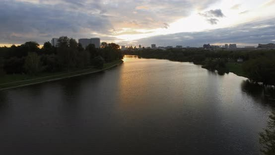 Thumbnail for An Aerial Evening View of a Wide River Surrounded By Dark Tree Crowns