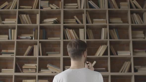 Thumbnail for Young Brunette Man Standing in Front of Bookshelves in Library and Choosing Literature. Camera Moves