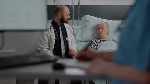 Doctor Talking to Retired Woman with Disease in Hospital Ward