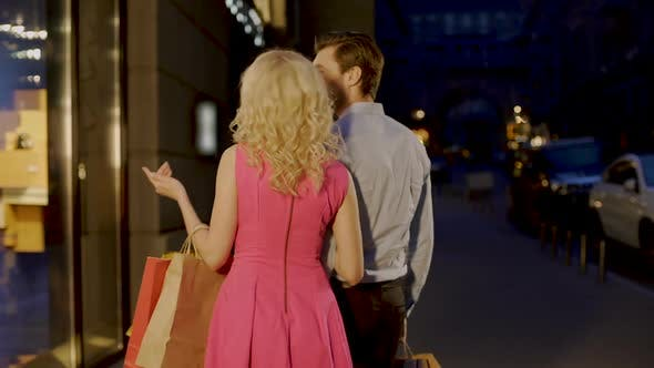 Cover Image for Beautiful Couple Strolling Through Evening Market Street Looking at Shop Windows