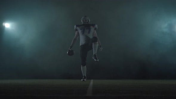 Thumbnail for American Football Sportsman Player in Football Helmet Standing on the Field on Black Background in a
