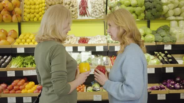 Thumbnail for Two Adult Women with Red and Yellow Bell Peppers Talking, To Camera and Smiling. Portrait of