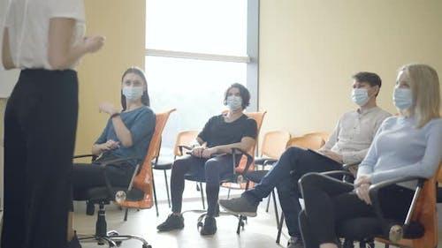 Unrecognizable Female Tutor Talking To Group of Adult Caucasian People Sitting in Auditorium