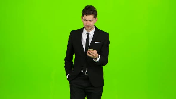 Thumbnail for Man Looks at the Photo on the Phone and Finds a List of Pictures. Green Screen