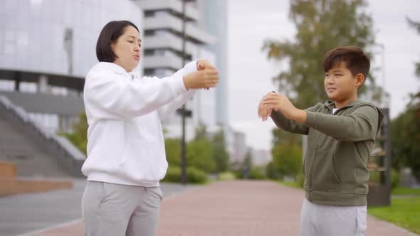 Thumbnail for Asian Woman and Boy Stretching Wrists during Outdoor Workout
