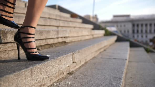 Legs in High Heels Stepping Down Stairs in City