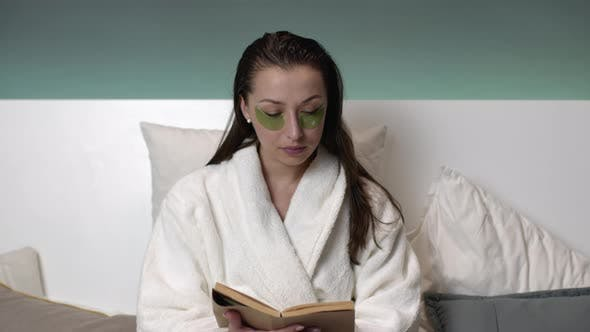 Thumbnail for Beautiful Girl in Bathrobe with Wet Hair, Patches on Eyes Reading Book on Bed