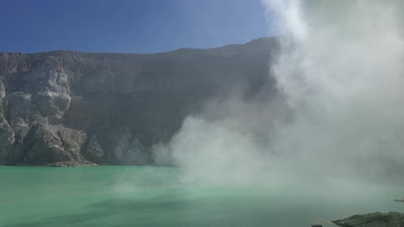 Thumbnail for Aerial view of flying above acidic lake and toxic sulfur gas clouds at the crater of Kawah Ijen