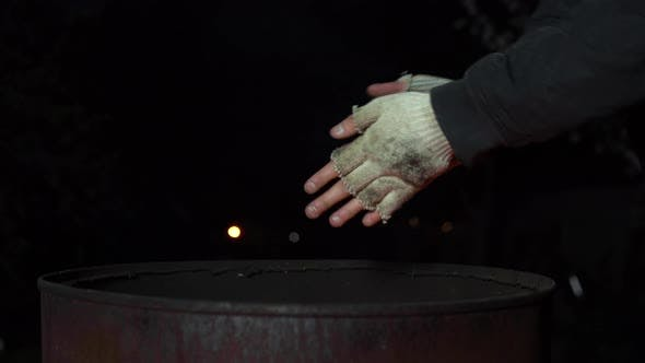 Thumbnail for A Homeless Man Warms His Hands at Night Near a Barrel of Fire. Hands Close Up.