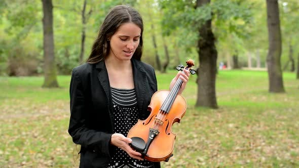Thumbnail for Young Happy Woman Describe Parts of Violin in the Forest - She Point Pieces of Violin and Talk
