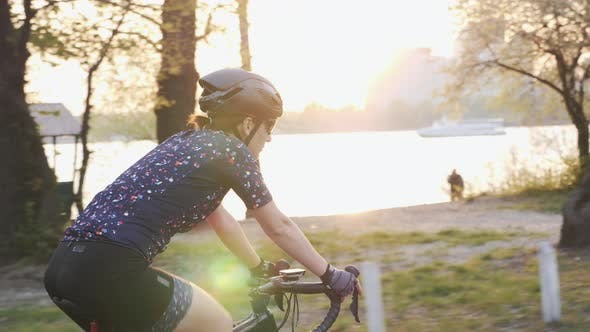 Thumbnail for Young Female Cyclist Riding Bicycle with River, City and Sunset on Background