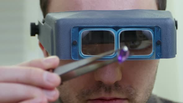 Thumbnail for Master Jeweler in Special Glasses Looking at Gem