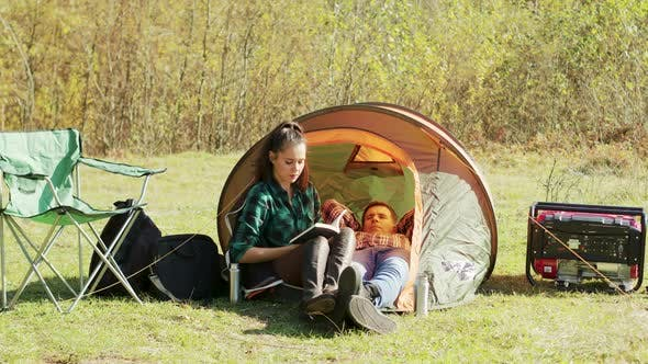 Thumbnail for Boyfriend Laying Down on Camping Tent While Girlfriend's Reading a Book