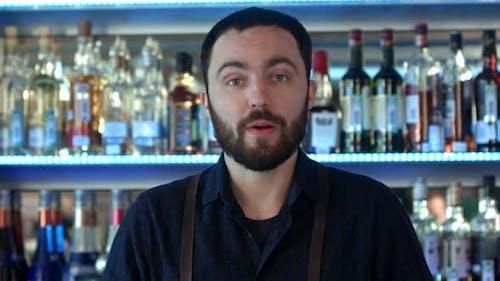 Positive Bartender Talking To a Camera at a Bar Counter