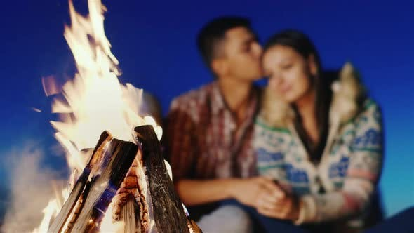 Cover Image for On the Beach, Lit a Fire in the Background Blurred Young Couple Embracing