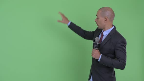 Thumbnail for Happy Bald Multi Ethnic Businessman As Newscaster Presenting Something
