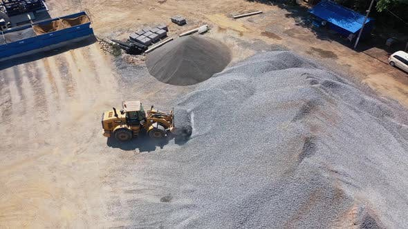 Asphalt plant with running bulldozer. The plant serves the needs of road construction.