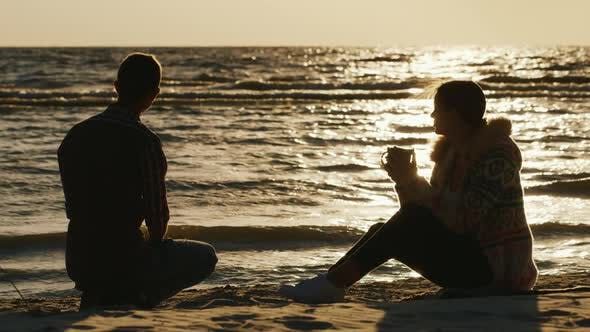Cover Image for Romantic Young Couple Relaxing on the Beach or a Lake on a Cool Day. Woman Drinking Tea From a Cup