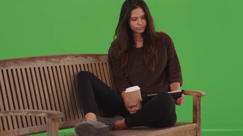 Pretty girl sitting and browsing online with portable tablet device greenscreen