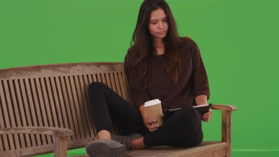 Thumbnail for Pretty girl sitting and browsing online with portable tablet device greenscreen