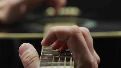 Fingers plating on the fretboard of a guitar