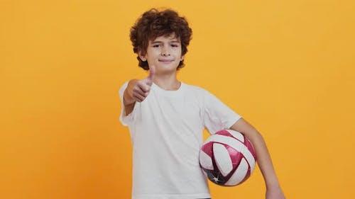 Kleiner Fußballspieler steht mit Fußball und gestikulierendem Daumen hoch, orangefarbener Studio-Hintergrund