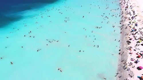 People Swim on Vacation in the White Sandy Beach of the Clear Tropical Turquoise Light Blue Sea
