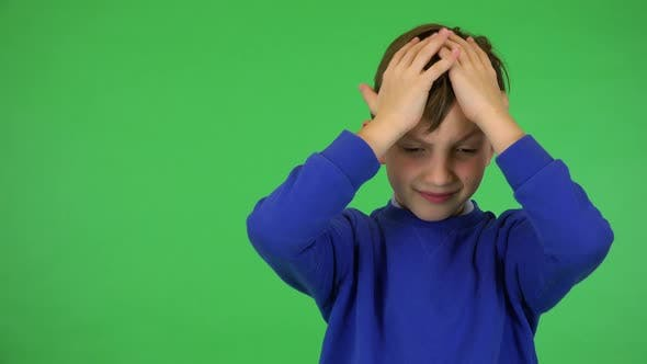 Thumbnail for A Young Cute Boy Hears a Piercing Noise, Frowns and Covers His Ears - Green Screen Studio
