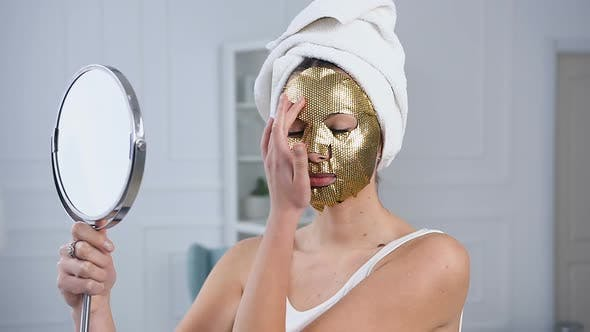 Thumbnail for Woman Fixing Rejuvenating Cosmetic Golden Tissue Mask on Face