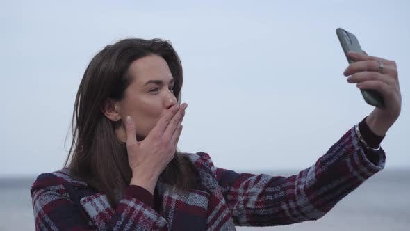 Thumbnail for Close-up of Cheerful Brunette Girl Sending Air Kiss at Selfie Camera. Young Positive Caucasian Woman