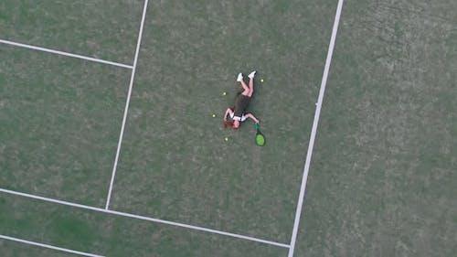 The girl lies on a tennis court